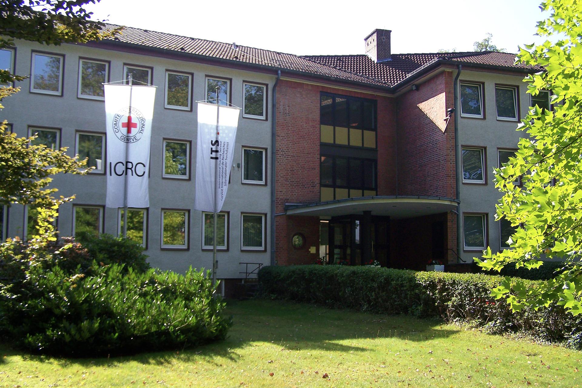 Kolorowe zdjęcie przedstawia duży budynek. Ściana frontowa. Budynek to parter idwa piętra. Dach budynku pokryty czerwoną dachówką. Spadzisty. Ściany budynku białe. Wejście do budynku zadaszone. Ściany przy wejściu inad wejściem pokryte czerwoną cegłą klinkierową. Naprzeciw budynku, po lewej stronie zdjęcia, dwa maszty zbiałymi flagami. Na flagach symbole. Na pierwszej fladze symbol czerwonego krzyża oraz napis czarnymi literami ICRC. Na drugie fladze symbol Unii Europejskiej. Przed budynkiem zielony trawnik imałe drzewka.