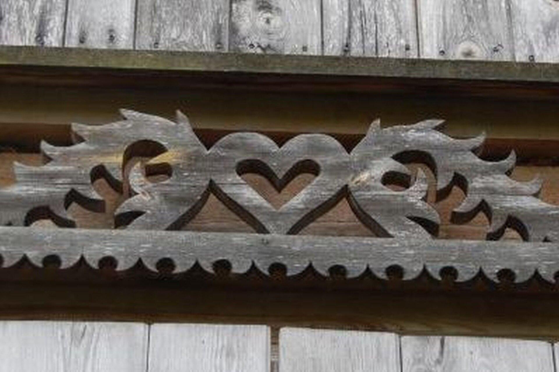 """Ilustracja przedstawia ozdobny drewniany element umieszczany nad oknem, tzw. """"korunę"""". Są to dwa ornamenty wpostaci zwiniętych motywów roślinnych, między którymi znajduje się serce."""