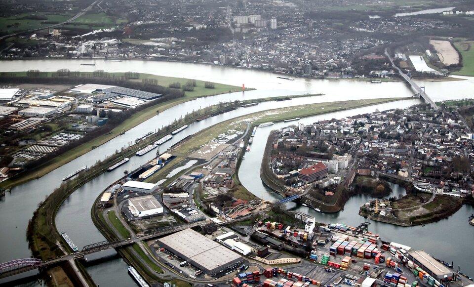 Na zdjęciu Zagłębie Ruhry. Teren gęsto zabudowany. Zakłady przemysłowe, magazyny, kontenery. Wtle zabudowania mieszkalne. Przez środek zdjęcia płynie rzeka, liczne odnogi, dopływy lub kanały.