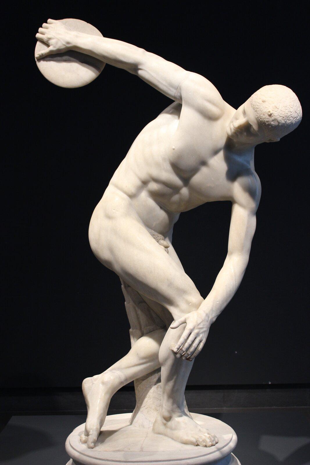 """Ilustracja przedstawia dzieło Myrona pt. """"Dyskobol"""". Rzeźba ta przedstawia nagiego mężczyznę skłaniającego się wkierunku ziemi, który wswojej prawej ręce trzyma dysk. Zgięte ciało oraz napięte mięśnie wskazują, że mężczyzna przygotowuje się do rzutu dyskiem."""