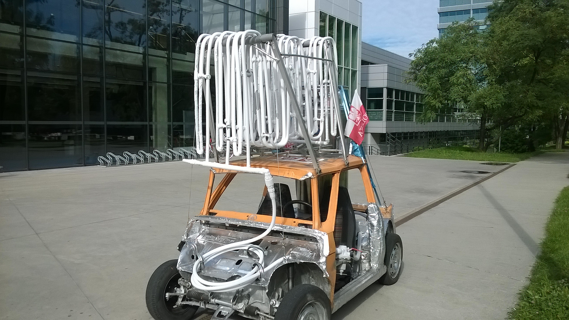 Zdjęcie przedstawia pojazd zbudowany na bazie szkieletu Fiata 126 pze skomplikowanym układem białych rurek na dachu. Gruby przewód od tych rurek biegnie do układu znajdującego się gdzieś pod srebrną częścią obudowy zocynkowanej stali lub aluminum. Pojazd ma dwa miejsca siedzące, jest pozbawiony szyb idrzwi. Stoi na betonowej płycie przed oszklonym budynkiem uczelni.