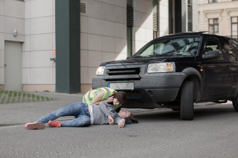 Zdjęcie przedstawia sytuację po wypadku wktórym samochód potrącił pieszego. Zdjęcie wykonano zniewielkiej wysokości nad poziomem jezdni. Po prawej stronie kadru znajduje się stojący na jezdni czarny samochód osobowy na tle bliżej nieokreślonych budynków. Przed samochodem, na asfalcie leży poszkodowana osoba, nastoletnia dziewczyna. Leży na boku, przodem do obserwatora zdjęcia. lewa noga wsparta na jezdni zgięta wkolanie, prawa wyprostowana, uniesiona ze stopą wspartą na jezdni. Obok leży zrzucony przez impet uderzenia but. Twarz nastolatki skierowana wgórę, głowa wsparta na ramieniu. Za plecami nastolatki kierowca samochodu, młoda kobieta znarzuconą na ubranie kamizelką odblaskową. Klęczy na jezdni ipochyla się nad twarzą poszkodowanej.