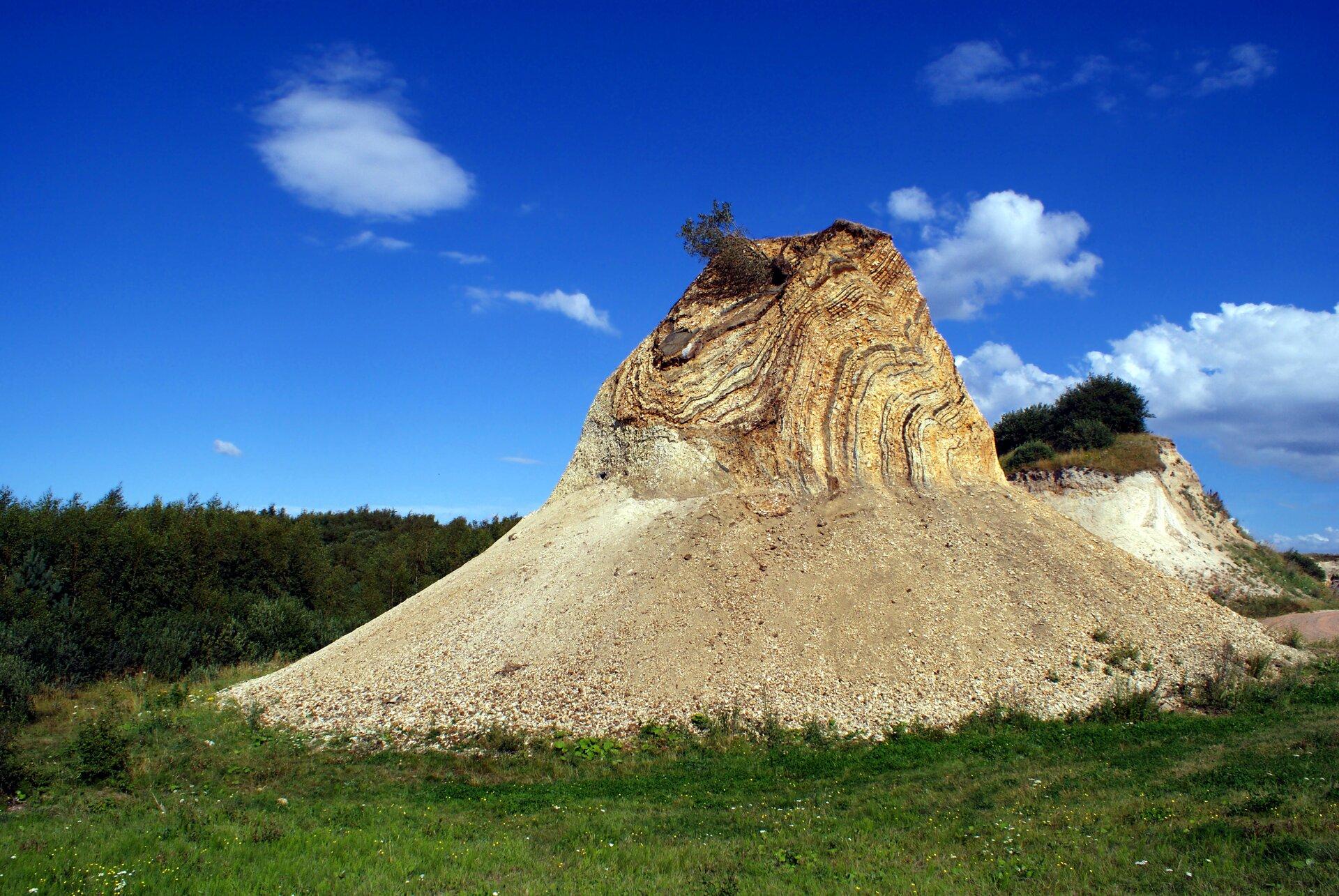 Zdjęcie przedstawia wysoką, kolumnową formację skalną przysypaną po bokach ziemią okrzemkową wsamym środku trawiastej równiny. Zdjęcie wykonano na duńskiej wyspie Fur znanej zbogatych pokładów tego typu ziemi oraz pięknych skamielin.