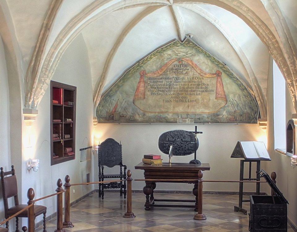 Sala wOpactwie Cystersów wOliwie Sala Pokoju - niewielka salka dawnego zimowego refektarza, gdzie 3 maja 1660 r., około północy po długich, sześć tygodni trwających debatach, podpisano pokój, który położył kres wojnom polsko-szwedzkim.Pomieszczenie znajduje się wpołudniowo-zachodniej części klasztoru. Do 1807 roku sala miała wystrój z1660 r. - fotele, kobierce iinne ozdoby. Wroku 1807 Francuzi zrabowali wszystkie pamiątki historyczne, pozostał tylko stół imalowidła ścienne.Na ścianie marmurowa tablica z1679 r. ku chwale róży herbowej (Poraj) Kęsowskich - pokój podpisano bowiem za urzędowania opata Aleksandra Kęsowskiego. Wyżej, na malowidle, widok opactwa oliwskiego, awtle Gdańska oraz po bokach wojskowych obozów: polskiego iszwedzkiego. Napis głosi chwałę dla Oliwy ifiołków, dających ojczyźnie kojący pokój w1660 r. - fiołki wzięły się prawdopodobnie ze swoistej gry słów. Łacińska nazwa tych kwiatków - Viola jest anagramem (wyrazem powstałym przez przestawienie liter bądź sylab innego wyrazu) łacińskiej nazwy miejscowości - Oliva. Źródło: Raimond Spekking, Sala wOpactwie Cystersów wOliwie, fotografia, licencja: CC BY-SA 4.0.