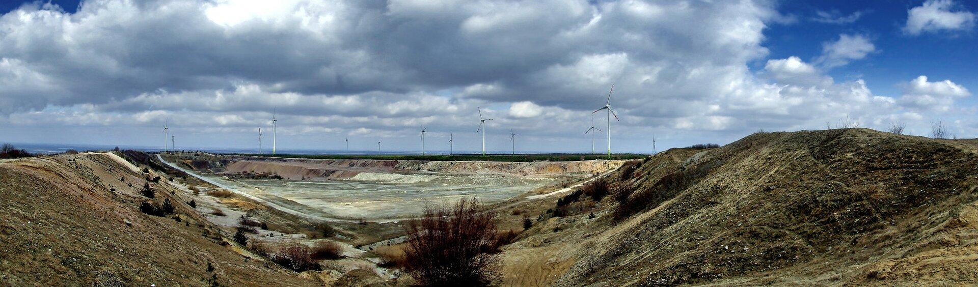 Fotografia prezentuje górę porośniętą trawą oraz krzewami.