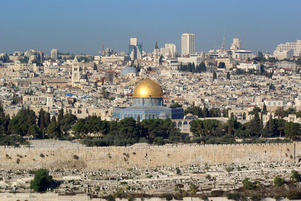 Na zdjęciu bardzo gęsta zabudowa, liczne świątynie, kopuły iwieże. Wtle wysokie budynki biurowe. Na pierwszym planie mur.