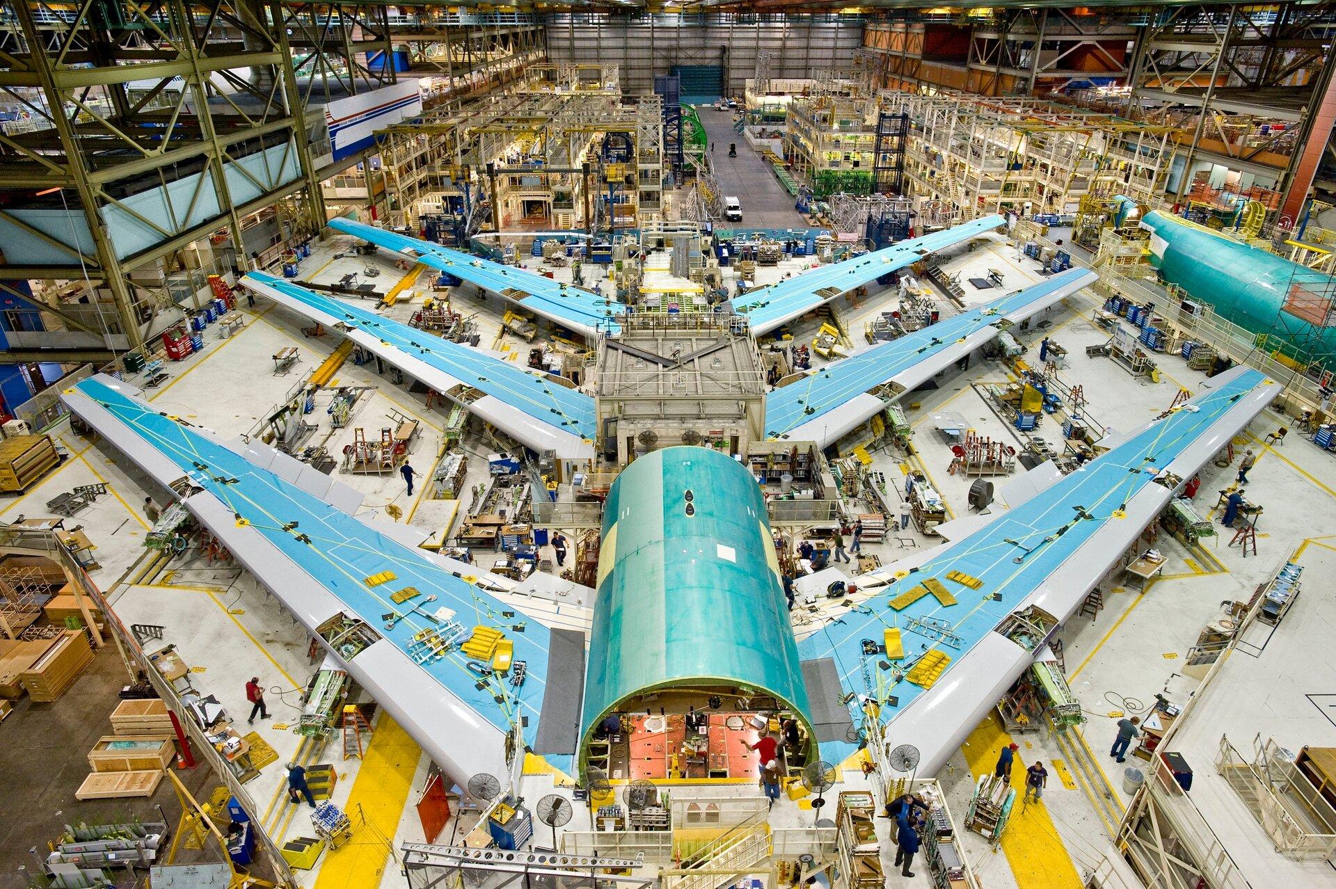 Na zdjęciu wnętrze dużej hali fabrycznej, kadłub iskrzydła samolotu, dookoła ludzie. Wtle rusztowania.