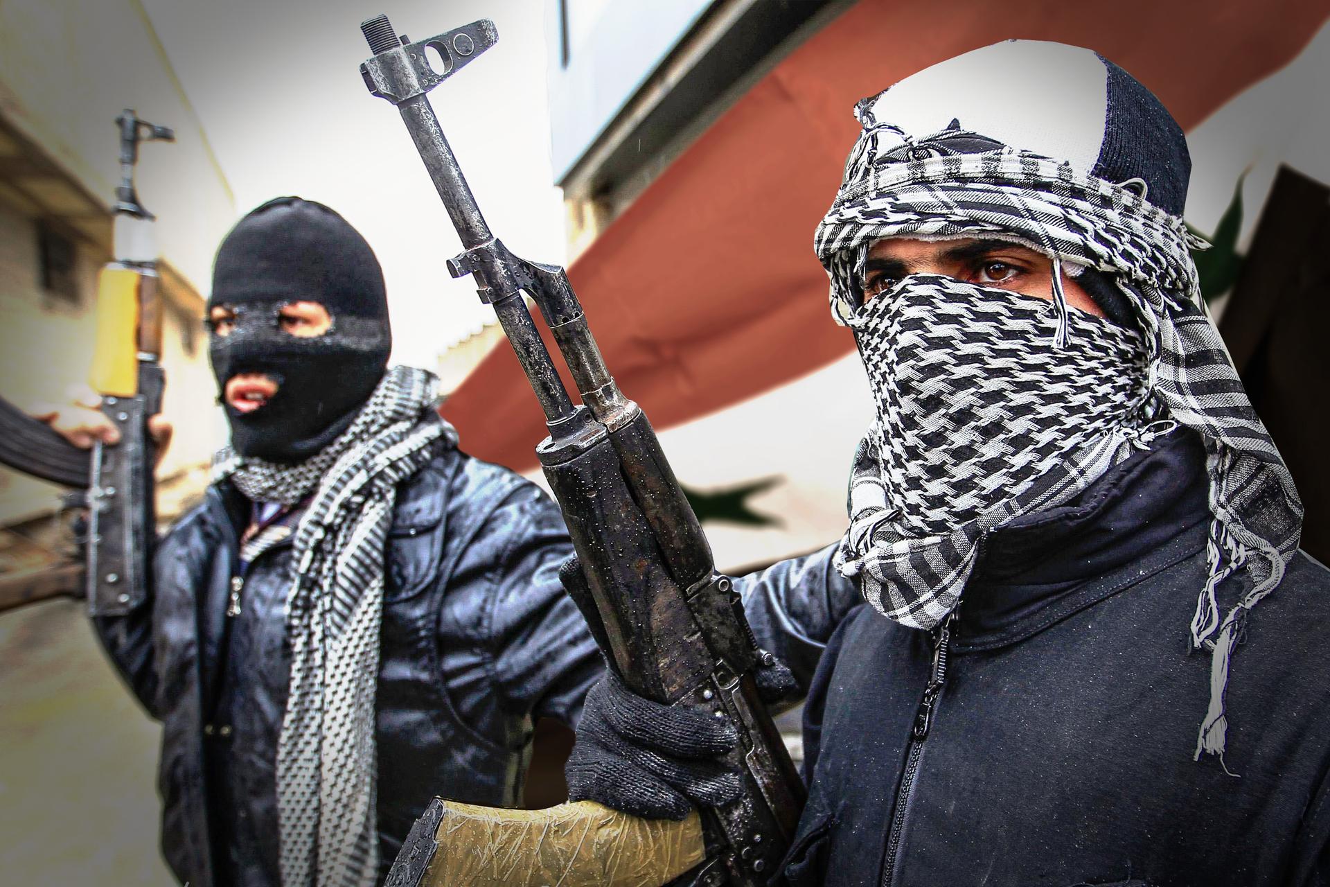 Kolorowe zdjęcie przedstawia dwóch mężczyzn stojących na ulicy. Mężczyźni mają zakryte twarze. Mężczyzna po lewej ma czarną kominiarkę. Mężczyzna po prawej białą czapkę ikraciastą chustę zawiązaną wokół twarzy. Wprawej ręce każdy trzyma karabin. Karabin skierowany lufą wgórę. Wtle, za mężczyznami, flaga Syrii. Po lewej budynki mieszkalne.