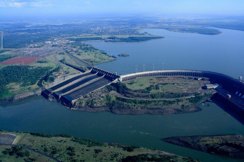 Na zdjęciu betonowa zapora na szerokiej rzece płynącej wpłaskim terenie.