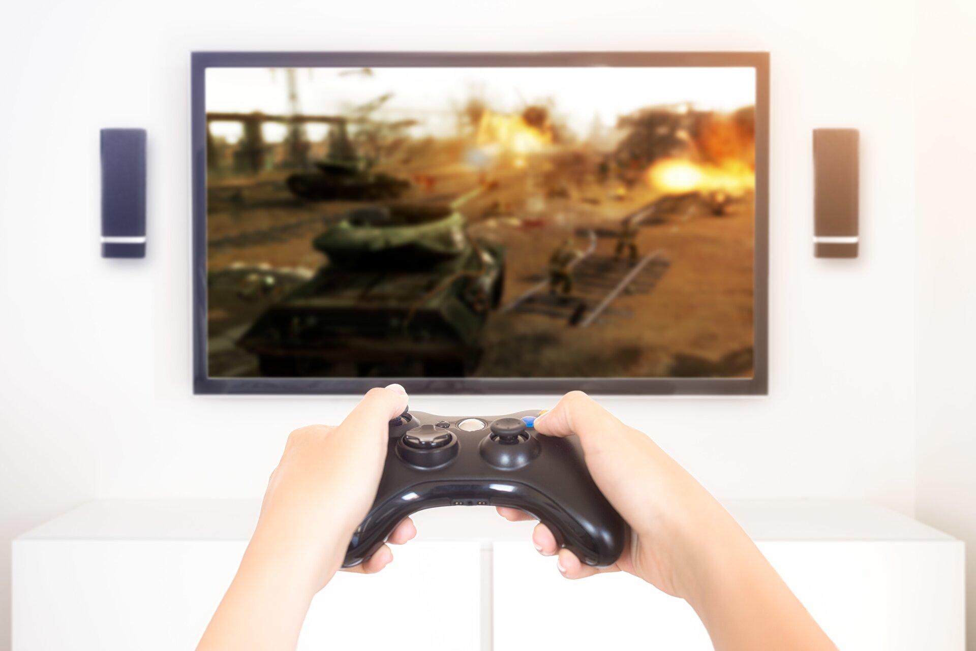 Ilustracja przedstawia granie na konsoli. Ukazuje ona osobę grającą wgrę na ekranie telewizora. Trzyma ona wdłoniach kontroler do gry.