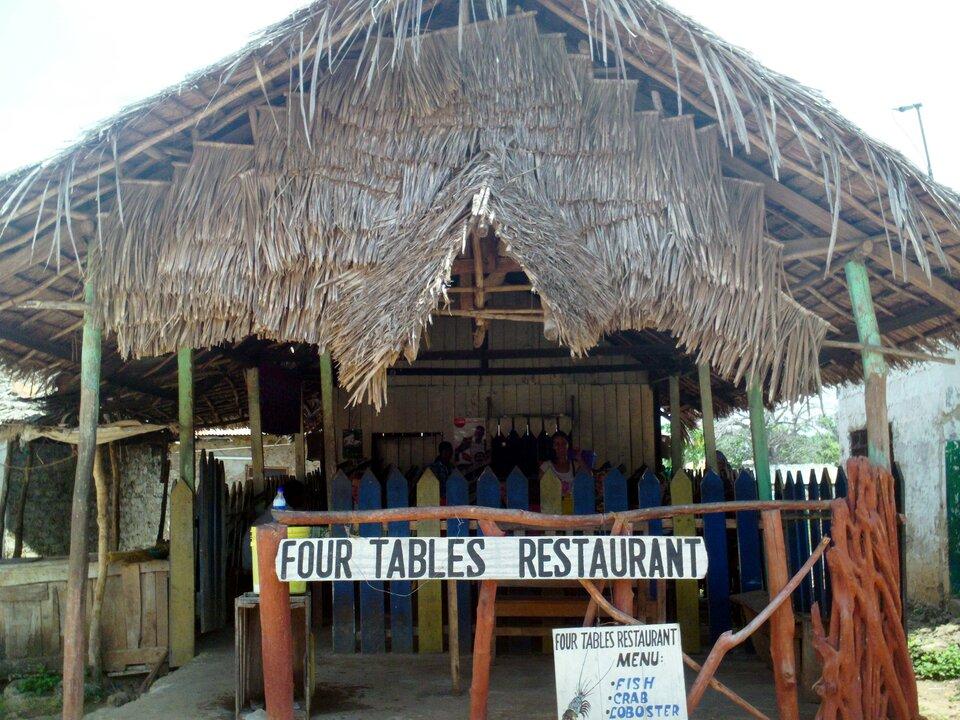 Na zdjęciu restauracja dla turystów. Lekka konstrukcja oparta na kilku drewnianych balach. Kryta deskami iliśćmi. Ogrodzona krótkimi palikami. Zprzodu napis znazwą restauracji.