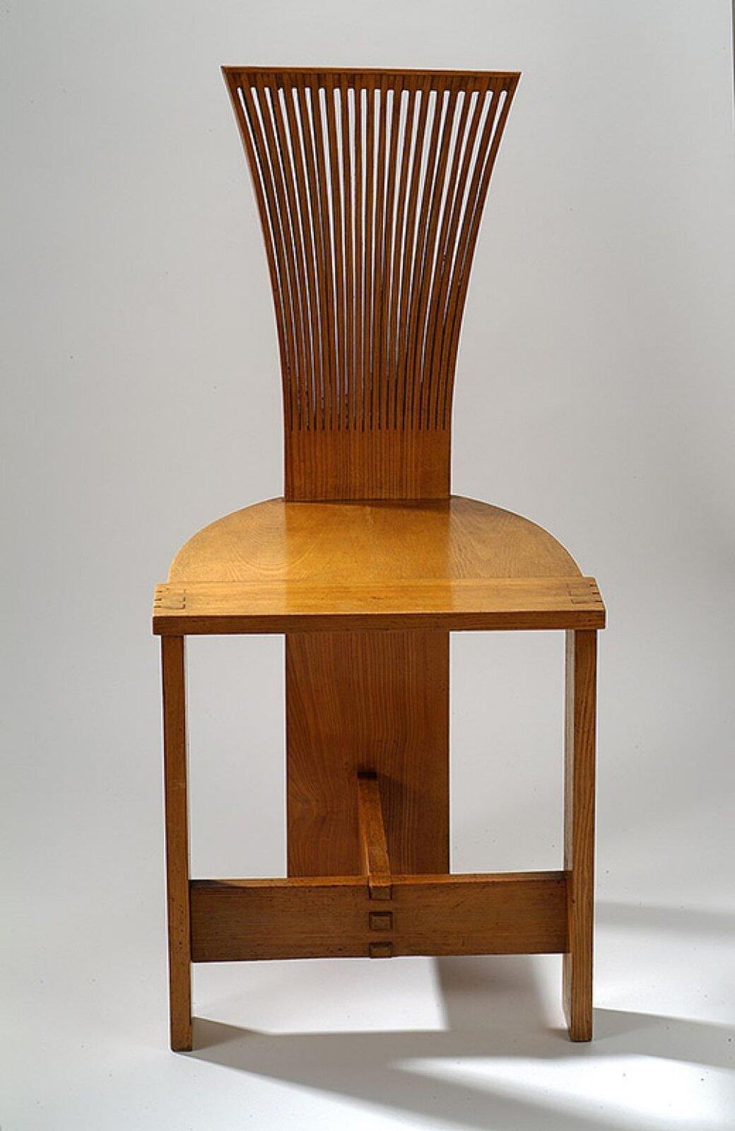 """Ilustracja przedstawia projekt Jana Kurzątkowskiego pt. """"Krzesło Piórka"""". Krzesło jest wykonane zdrewna ojasno brązowym kolorze. Oparcie wygląda jakby było zrobione zcienkich listewek szersze ugóry, awęższe przy części do siedzenia. Oparcie chodzi aż do ziemi stanowiąc trzecią nogę krzesła. Udołu pod częścią do siedzenia są dwie prostopadle do siebie połączone deski stanowiące umocnienie konstrukcji krzesła."""