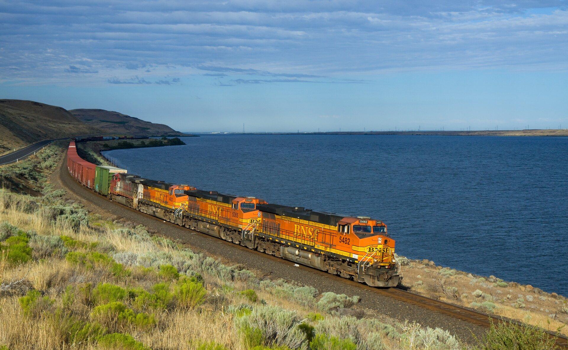 Na zdjęciu pociąg towarowy. Cztery lokomotywy, kilkanaście wagonów. Brak sieci trakcyjnej. Pociąg jedzie wzdłuż wybrzeża, po prawej stronie wtle morze. Na pierwszym planie krzaczasta roślinność. Po lewej stronie równolegle do linii kolejowej droga. Wzdłuż drogi pasmo gór.