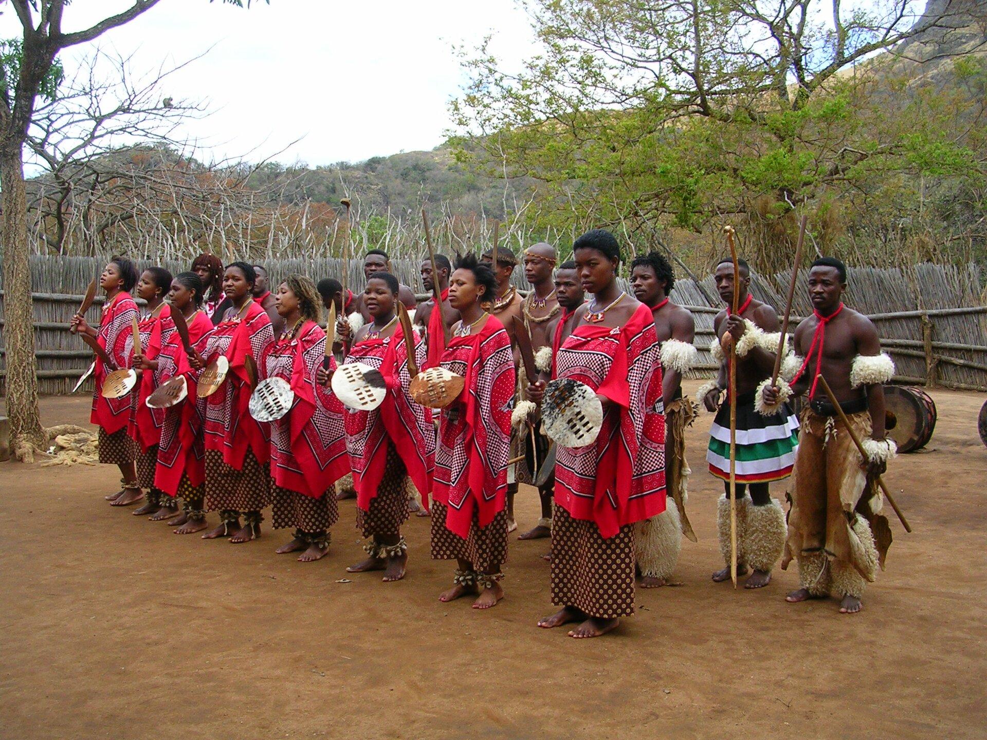 Na zdjęciu plemię afrykańskie. Wpierwszym rzędzie kobiety ubrane wdługie spódnice iczerwone luźne chusty. Trzymają wrękach tarcze inoże. Wdrugim rzędzie mężczyźni, ubrani wspodnie lub spódnice. Na ramionach iłydkach mają ozdoby zfutra iskór. Wrękach trzymają długie kije. Wtle ogrodzenie zsuchych gałęzi, za ogrodzeniem drzewa.