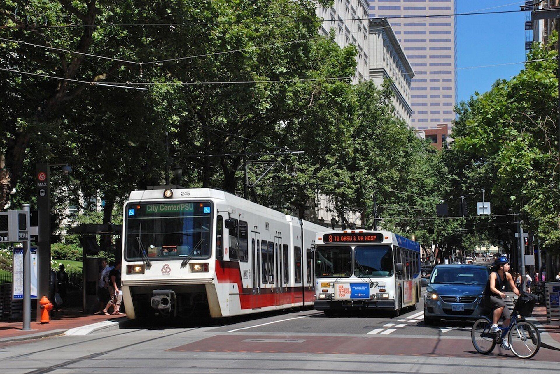 Fotografia przedstawia ulicę wPortland. Słoneczny dzień, jadący rowerzysta, tramwaj, autobus, zielone drzewa.