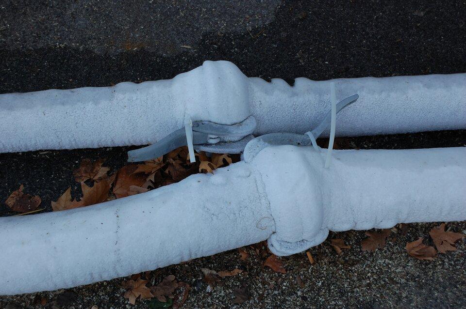Zdjęcie przedstawia pokryte lodem rury. Fotografia ma orientację poziomą, awykonano ją wzimie. Dwie rury wodociągowe ułożone są równolegle do siebie, acentralną część kadru zajmują znajdujące się na nich klamry łączące dwie części rury zaopatrzone wzaciski unieruchomione plastikowymi opaskami. Pod rurami znajduje się gleba iopadłe liście, co wskazuje na to, że rury poprowadzone są na zewnątrz zabudowań.