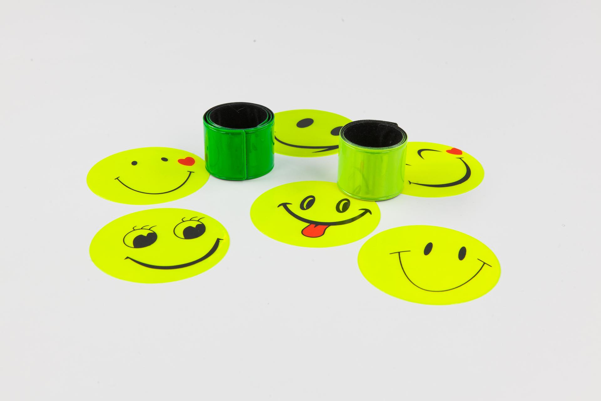 Galeria zawierająca zdjęcia przyborów odblaskowych poprawiających widoczność człowieka na drodze. Zdjęcie numer dwa przedstawia naklejki iopaski odblaskowe. Okrągłe naklejki przedstawiają uśmiechnięte buźki. Elastyczne opaski przeznaczone do zakładania na nadgarstki ułożone wrulony. Dominujące kolory akcesoriów to żółć izieleń.