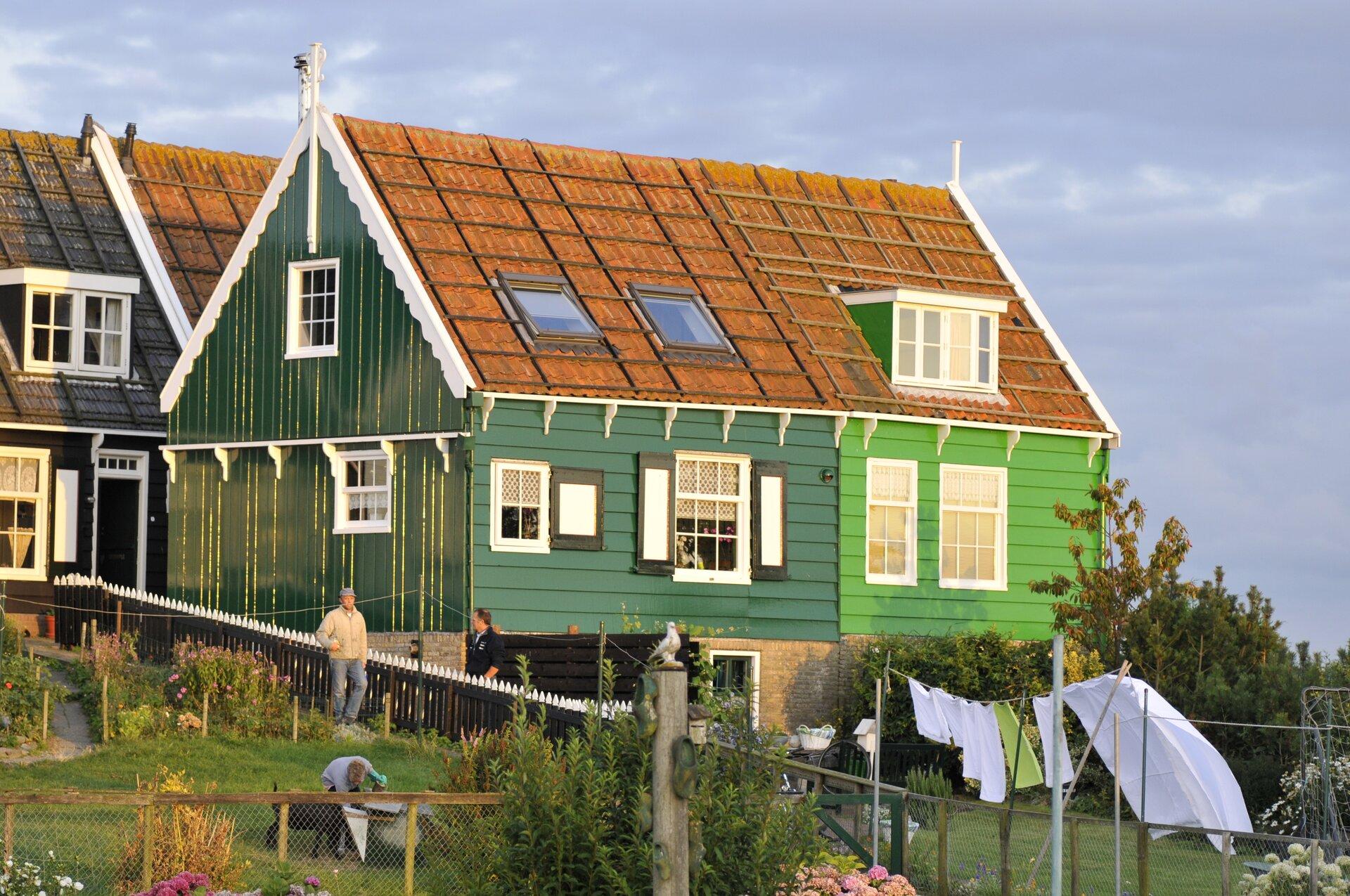 Na zdjęciu wiejska zabudowa. Zielony drewniany dom zbiałymi elementami. Dach kryty czerwoną dachówką. Teren ogrodzony, przy płocie stoją ludzie. Wogrodzie suszy się pranie. Wtle drugi podobny dom.