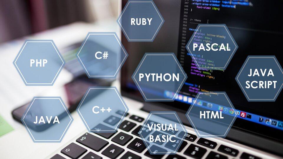 """Ilustracja pokazuje zdjęcie przedstawiające fragment monitora komputerowego ilewy górny róg leżącej przed nim klawiatury. Na czarnym ekranie komputera widać wedytorze linie kodu programu komputerowego. Wzdjęcie wkomponowano dziesięć niebieskich sześciokątów. Wewnątrz każdego znich wpisano białą czcionką nazwy przykładowych języków programowania: """" PHP, JAVA, C#, C++, RUBY, PYTHON, PASCAL, HTML, JAVA SCRIPT""""."""