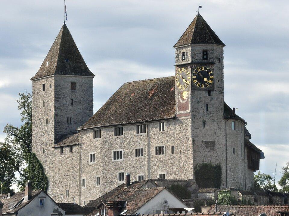 Na zdjęciu średniowieczny zamek zdwoma wieżami. Na prawej wieży zegar.