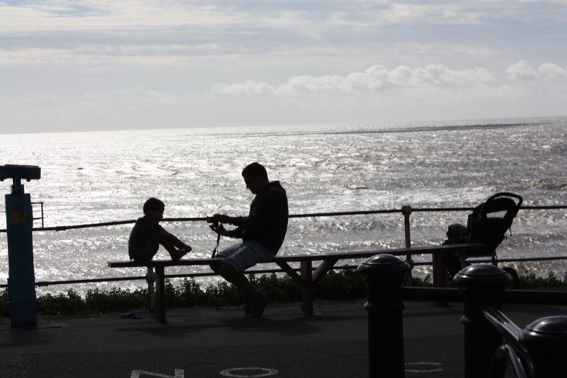 Fotografia nieznanego autora przedstawia dwie osoby odpoczywające nad morzem – ojca isyna, którzy siedzą na ławce. Chłopiec siedzi zlewej strony ławki, nogi trzyma na siedzisku. Jego ojciec siedzi na środku ławki, wdłoniach trzyma aparat, którym wykonuje zdjęcie.