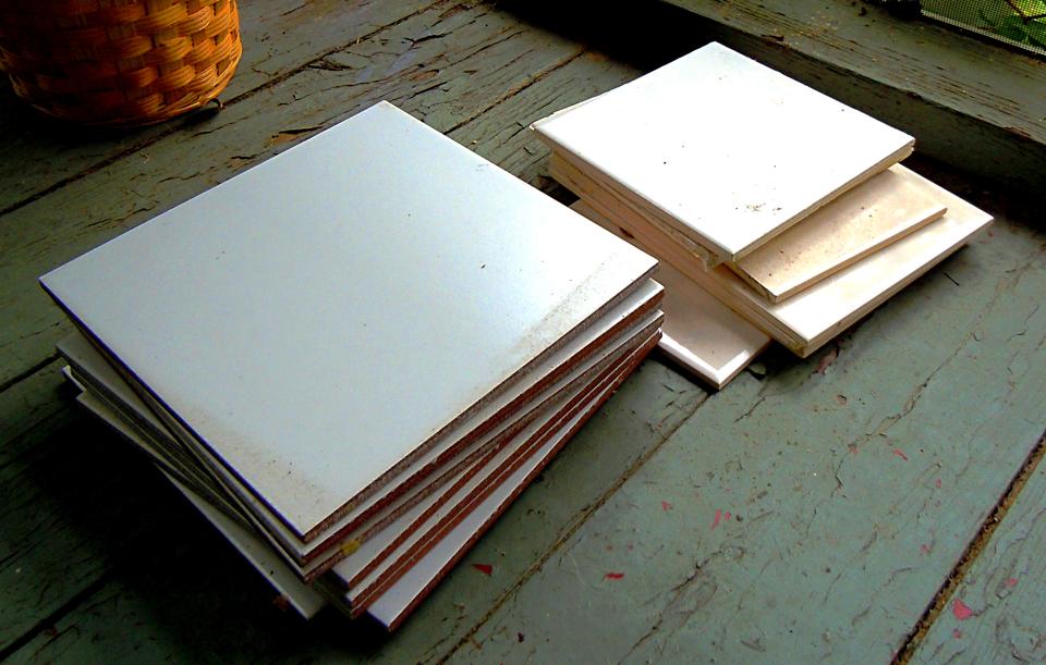 Zdjęcie przedstawia białe płytki ceramiczne ułożone wdwóch stosach po około dziesięć płytek na starej, drewnianej podłodze. Stos po lewej stronie to płytki większe, prawdopodobnie podłogowe. Stos po prawej zawiera płytki mniejsze, ścienne.