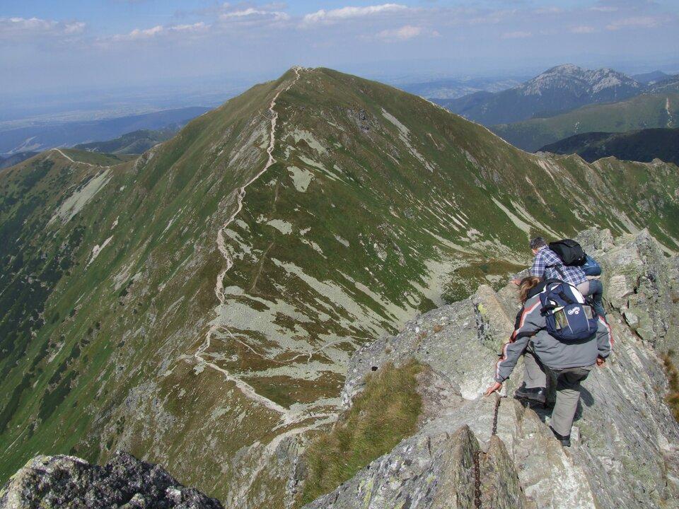 Na zdjęciu turyści na wysokogórskim szlaku idą po skalistym szczycie trzymając się łańcuchów.