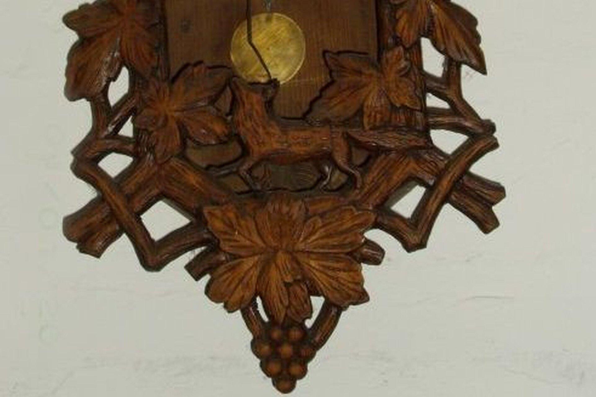 Ilustracja przedstawia fragment drewnianego ludowego zegara. Jest zdobiony motywami liści. Wgórnej części znajduje się wahadło, pod nim, na środku umieszczony jest lis. Udołu zegar jest dekorowany kiścią winogrona.