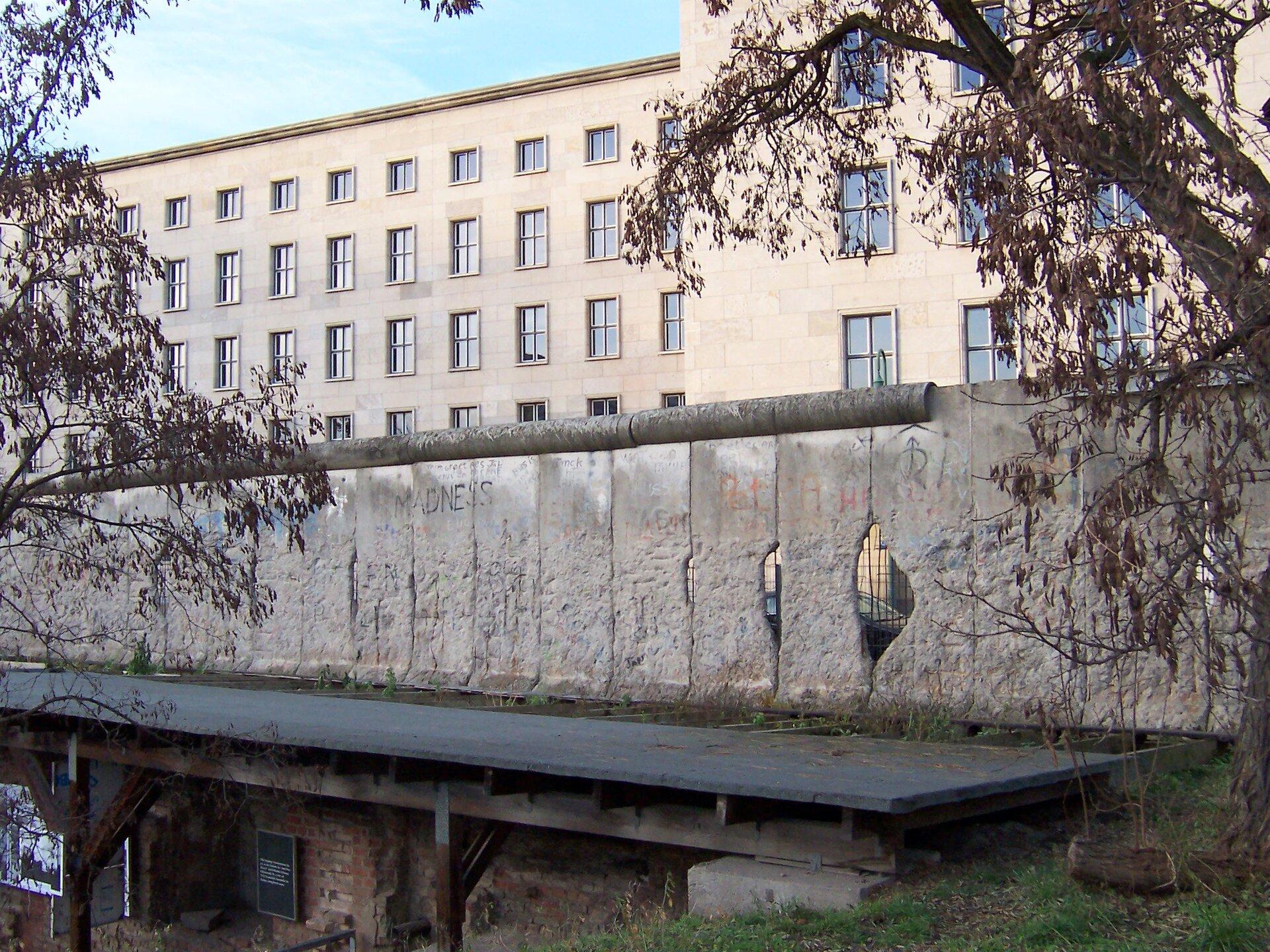 Na zdjęciu wysoki betonowy mur, gdzieniegdzie dziury, widać metalowe zbrojenia. Za murem kilkupiętrowy kamienny budynek.
