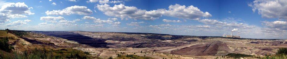 Na zdjęciu kopalnia węgla brunatnego. Rozległe wyrobisko, wiele hałd, liczne głębokie wykopy. Na horyzoncie po prawej stronie widoczna elektrownia.