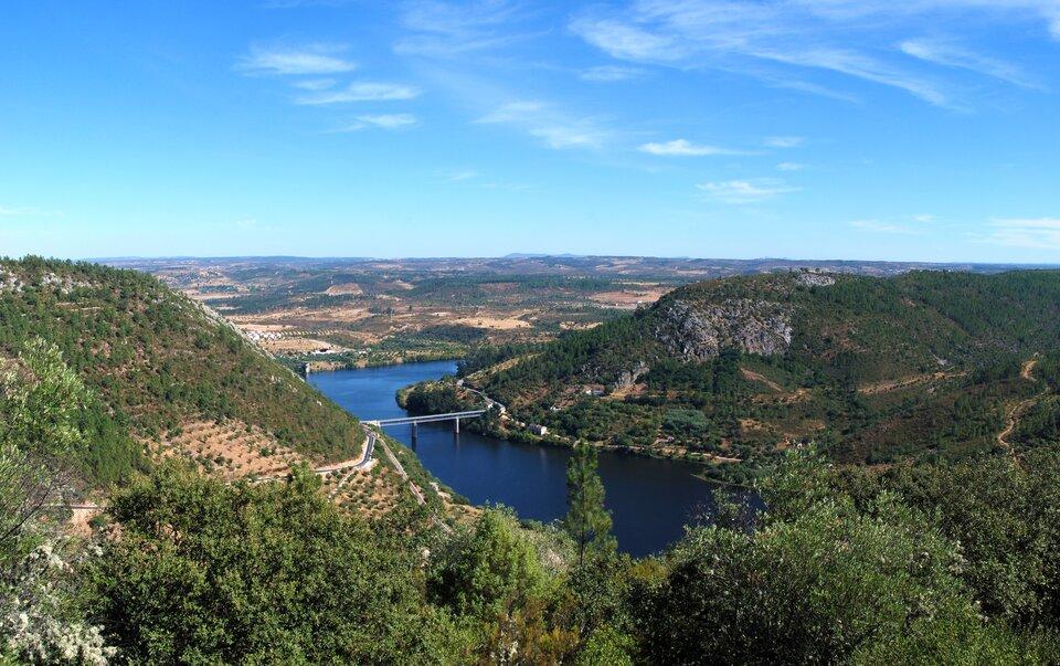 Na zdjęciu rzeka wterenie górzystym. Góry łagodne, porośnięte lasami ipokryte plantacjami równo zasadzonych roślin. Most.