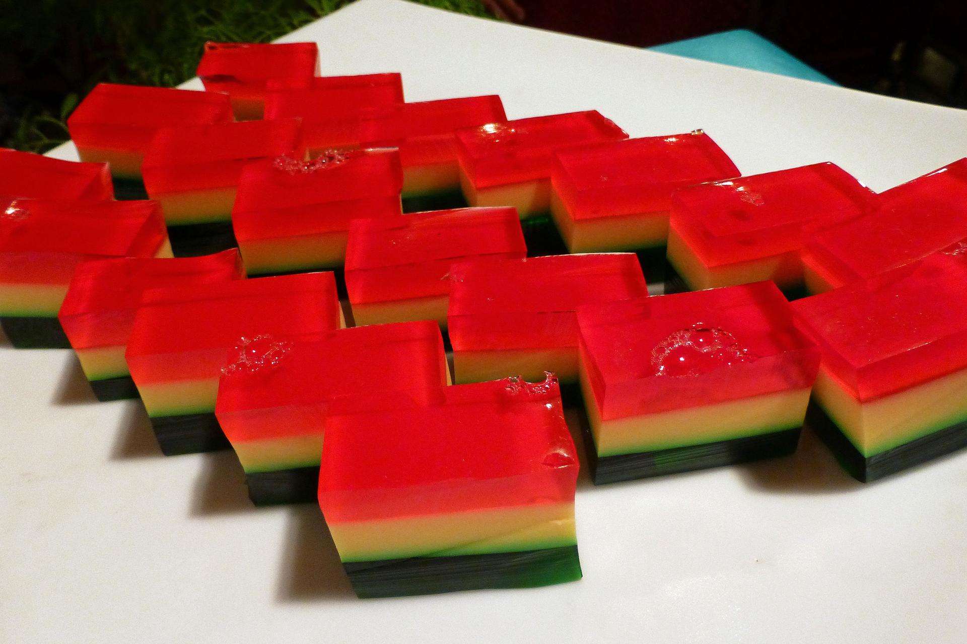 Fotografia przedstawia kilkanaście kawałków galaretki, złożonej ztrzech warstw. Od góry; czerwonej, wśrodku kremowej ina dole ciemno zielonej. Do produkcji słodyczy wykorzystuje się między innymi agar – agar, środek żelujący pozyskiwany zglonów.