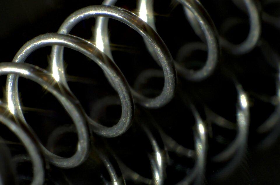 Zdjęcie przedstawia stalową sprężynę na czarnym tle odbijającym obraz przedmiotu. Sprężyna jest naciągnięta iułożona ukośnie względem kadru.