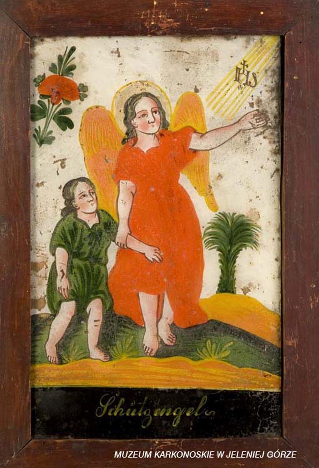 Ilustracja przedstawia malowidło na szkle, które ukazuje anioła prowadzącego za rękę dziecko. Anioł ma pomarańczową szatę, alewą ręką wskazuje na promienie boskie znapisem IHS. Dziecko jest ubrane wzieloną szatę. Wtle widać drzewo palmowe iczerwony kwiat.