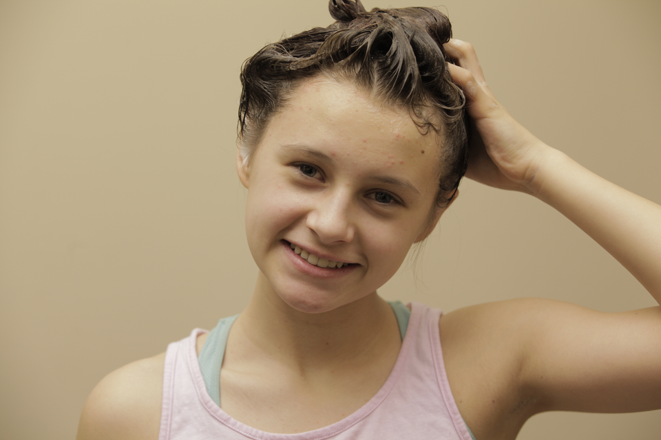 Fotografia przedstawiająca młodą dziewczynę myjącą włosy