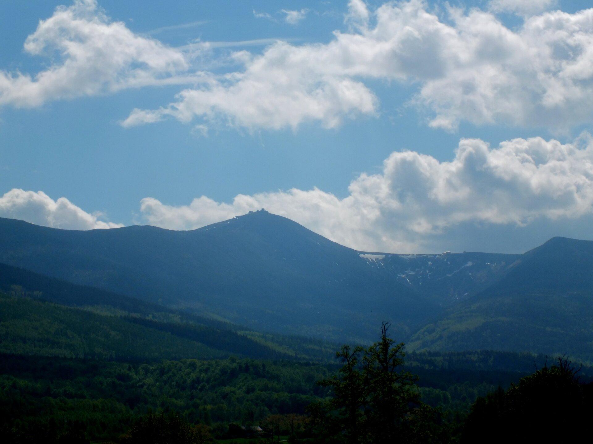 Na zdjęciu pasmo górskie zwyraźnym wzniesieniem pośrodku. Na szczycie zabudowania. Na pierwszym planie pofałdowany teren porośnięty lasem.