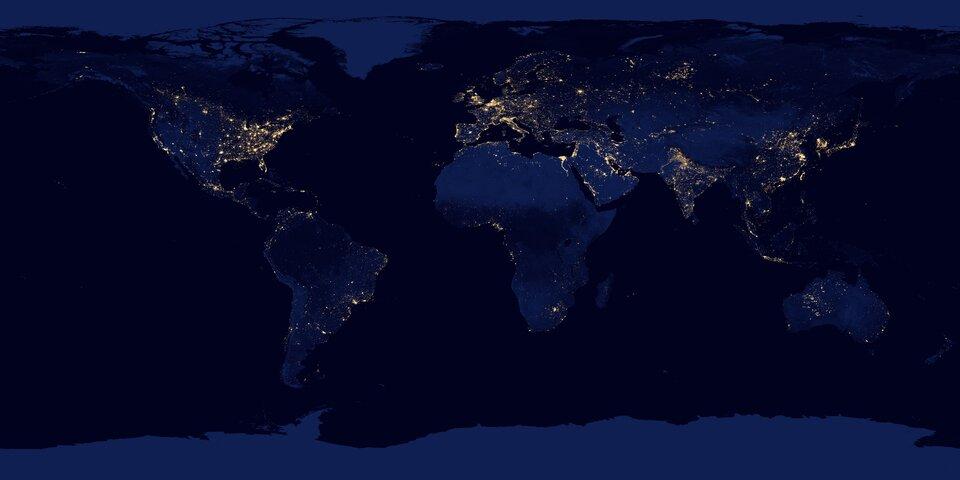 Satelitarne zdjęcie Ziemi wykonane nocą. Prostokąt zoceanami ikontynentami. Oceany bardzo ciemne, prawie czarne. Kontynenty jaśniejsze – granatowe. Na kontynentach pojedyncze światła, łączące się wrozświetlone obszary. Obszary oświetlone pokrywają się zobszarami gęsto zaludnionymi. Wyjątek stanowią gęsto zaludnione, ale niezelektryfikowane obszary Afryki Subsaharyjskiej.