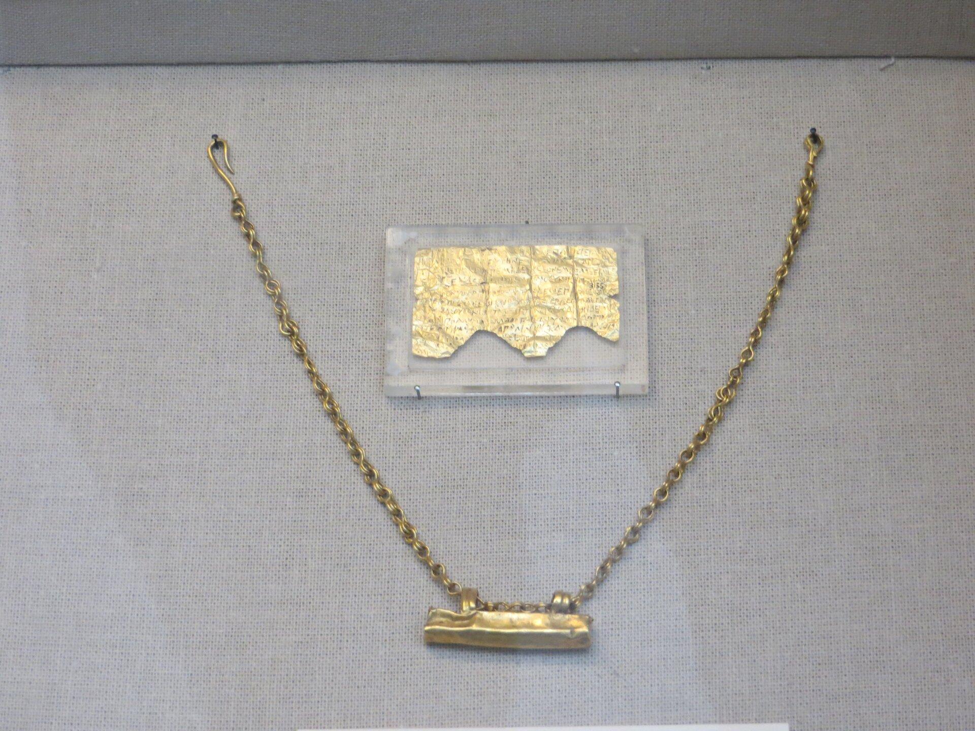 Ilustracja przedstawia fragment złotej tabliczki orfickiej zIII/II w. p.n.e. Tabliczka zachowała się wzłym stanie, ma nierówne zniszczone brzegi. Wokół niej rozłożony jest złoty łańcuch, na którym prawdopodobnie została zawieszona.