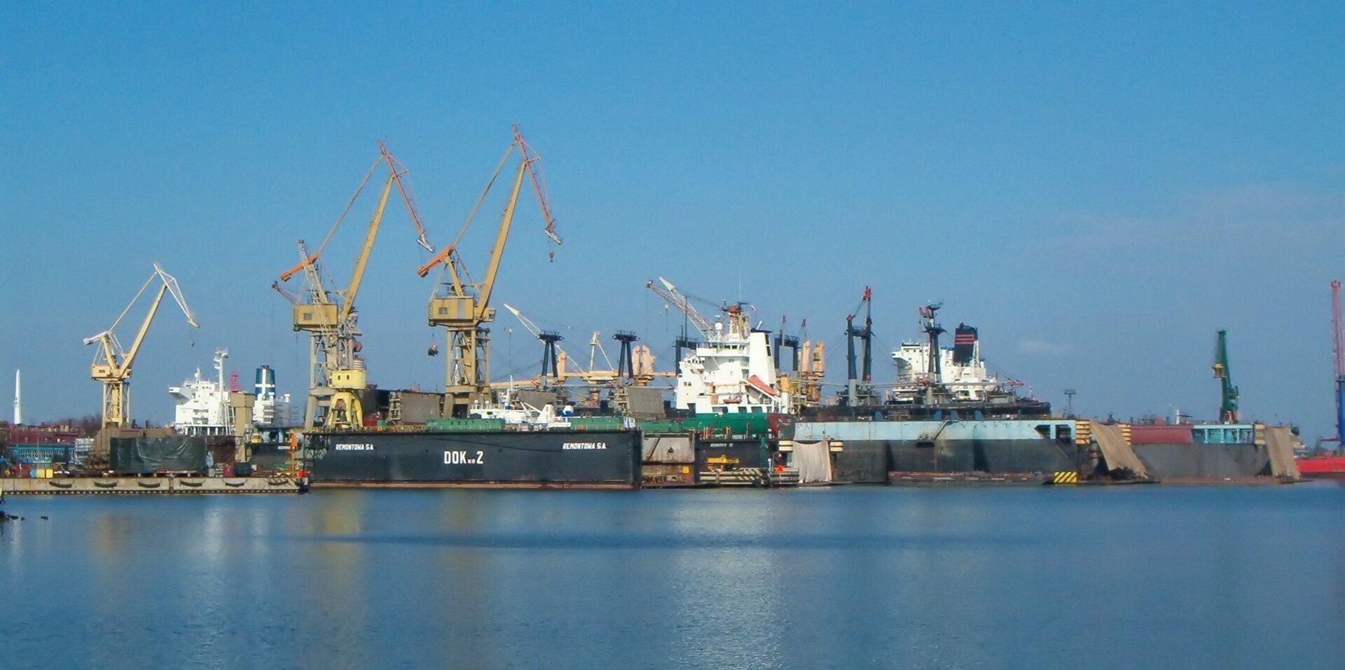Na zdjęciu stocznia remontowa, liczne zabudowania portowe, dźwigi, kilka statków.