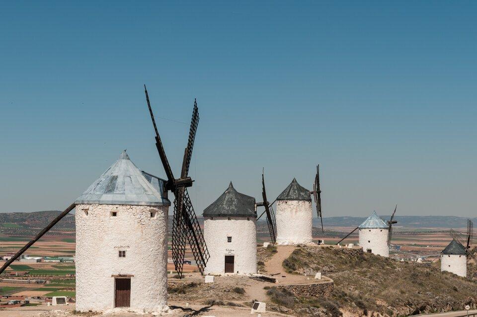 Na zdjęciu pięć białych okrągłych wiatraków otynkowanych na biało ustawionych wszeregu jeden za drugim na górzystym terenie. Wtle pola uprawne, dalej góry.