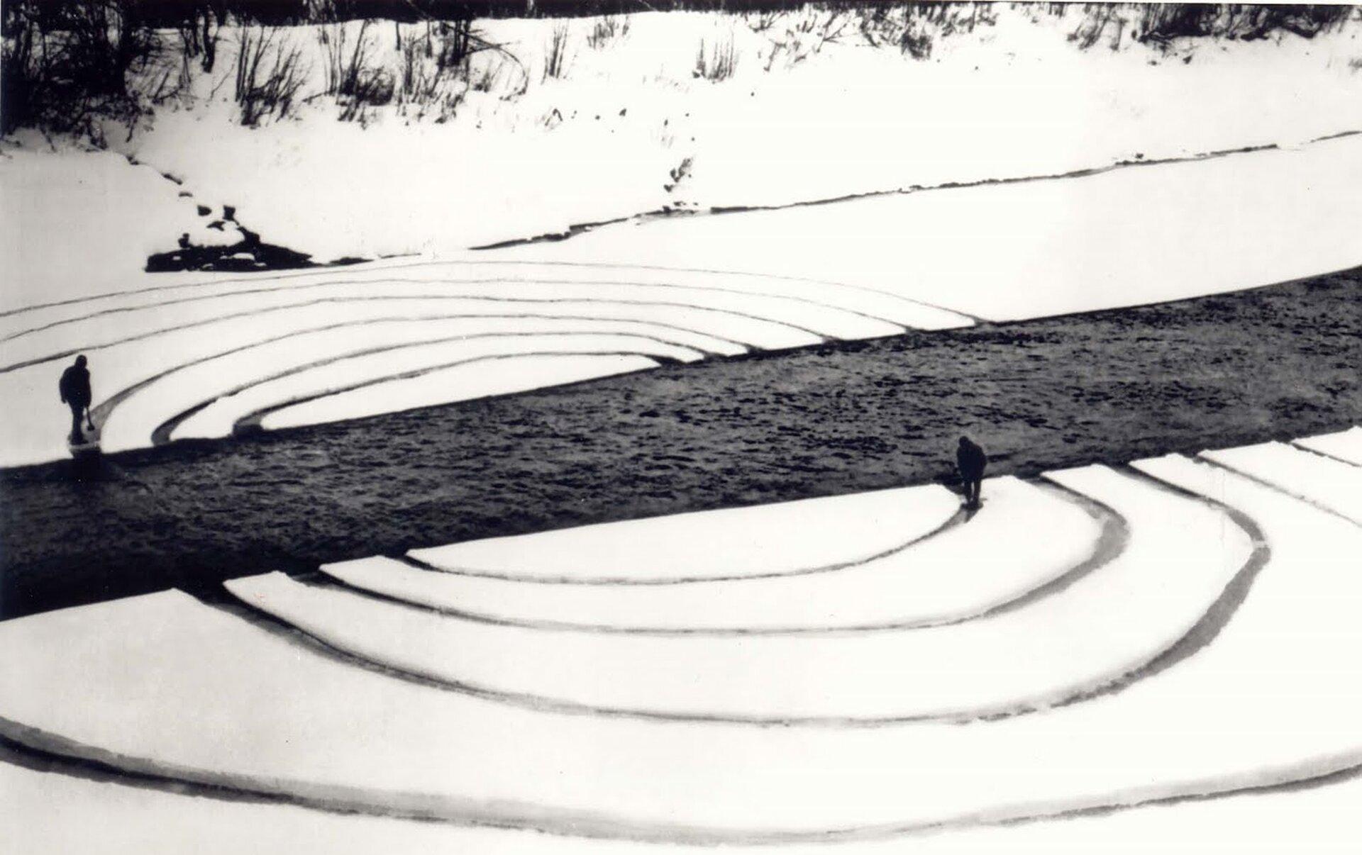 Ilustracja przedstawia pierścienie, które są przecinane przez rzekę. Pierścienie są zrobione na śniegu. Prace artysty odnoszą się do naturalnych procesów zachodzących wprzyrodzie inietrwałości, ulotności dzieł stworzonych przez człowieka.