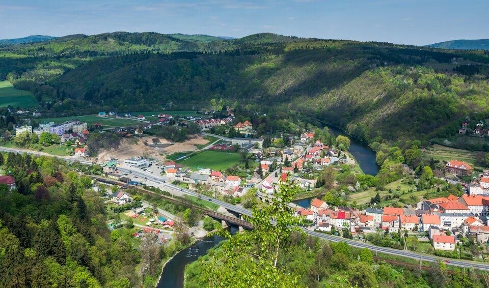 Na zdjęciu kręta rzeka wdolinie, której zbocza porastają lasy mieszane. Nad rzeką zabudowa miejska.