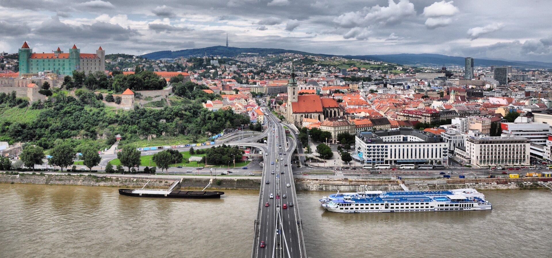 Widok zlotu ptaka na Stare Miasto wBratysławie. Na pierwszym planie most, rzeka, statek wycieczkowy.