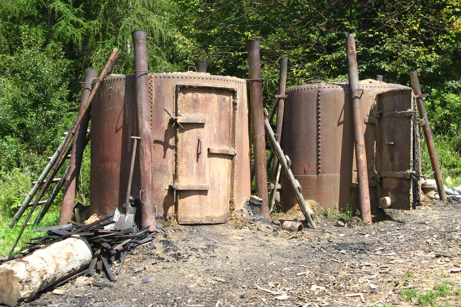Na fotografii widoczne dwa metalowe, okrągłe piece zdużymi drzwiami, wktórych wytwarza się węgiel drzewny.