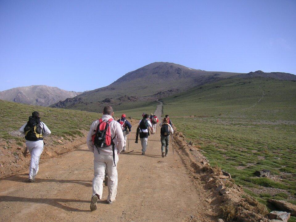 Na zdjęciu łagodne góry. Na pierwszym planie drogą idą turyści.