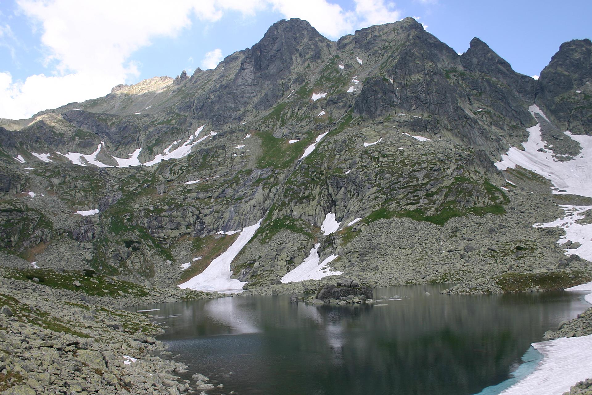 Fotografia ukazująca panoramę gór wysokich nad jeziorem, Morskim Okiem. Widoczne cztery szczyty górskie, zktórych najwyższy po lewej stronie, to Rysy. Stoki szczytów gdzieniegdzie są pokryte śniegiem.