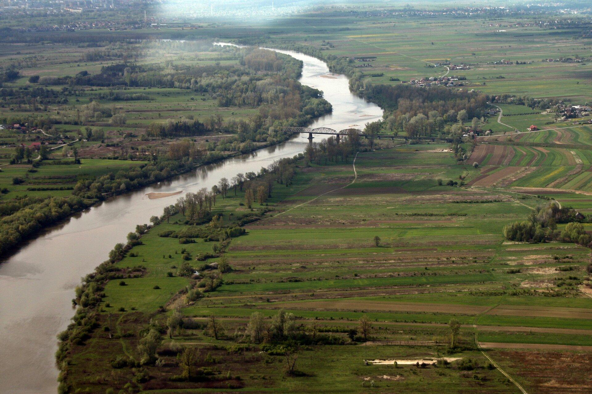 Na zdjęciu płaska dolina, rzeka, tereny zielone.