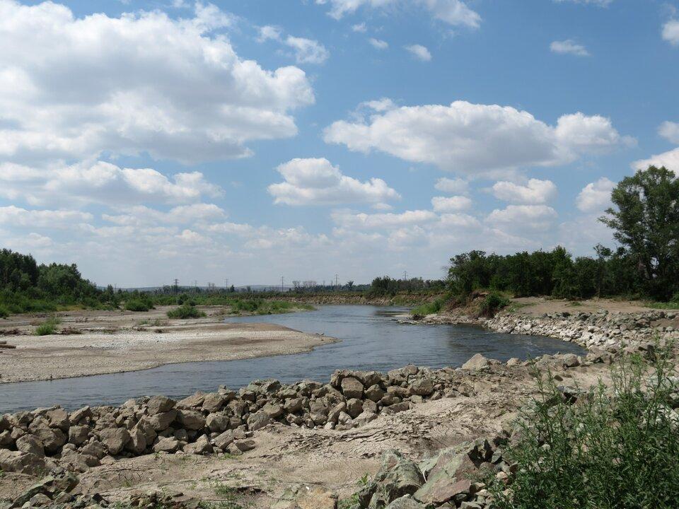 Na zdjęciu rzeka, kamieniste brzegi, dalej od brzegów drzewa.
