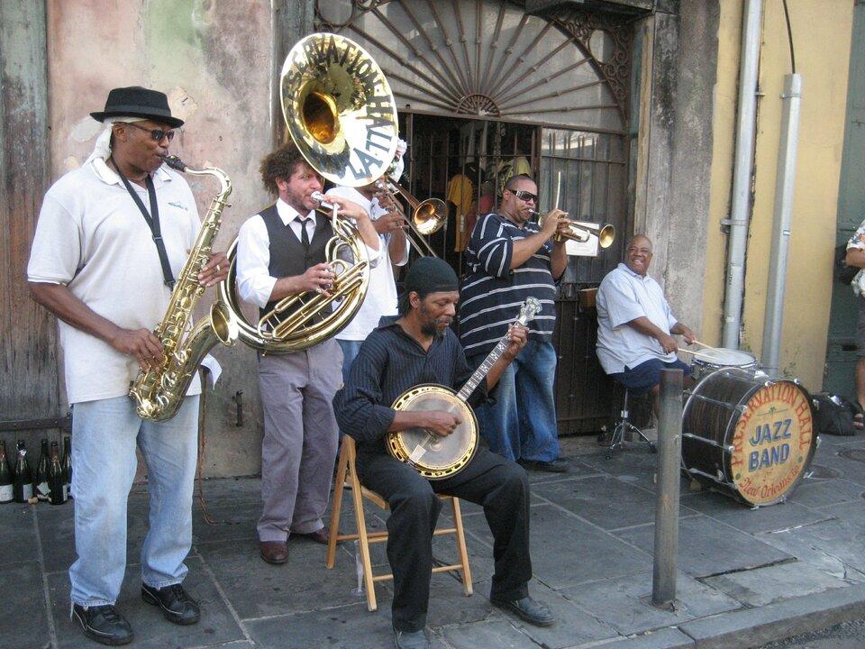 Na zdjęciu kilku muzyków gra na różnych instrumentach. Stoją na chodniku przed wejściem do budynku.