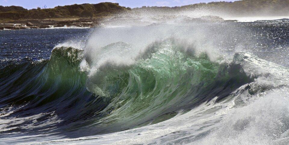 Zdjęcie przedstawia falę morską zbliska. Czoło fali wygięte wlewo zwidocznym wgórnej części spienionym zawinięciem, woda podświetlona światłem słonecznym wkolorze szmaragdowym, udołu fali ciemnoniebieska. Wtle spokojna powierzchnia morza oraz skalisty brzeg.